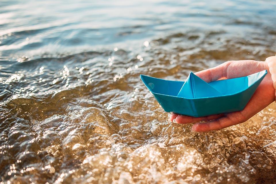 Kind mit blauem Papierboot